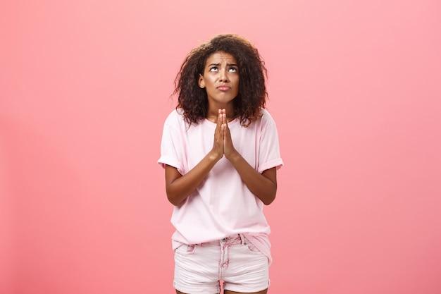 ピンクの壁を祈って見ているアフリカ系アメリカ人の女性