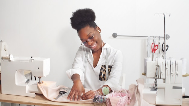 African american female professional fashion designer working on fabric in a workshop