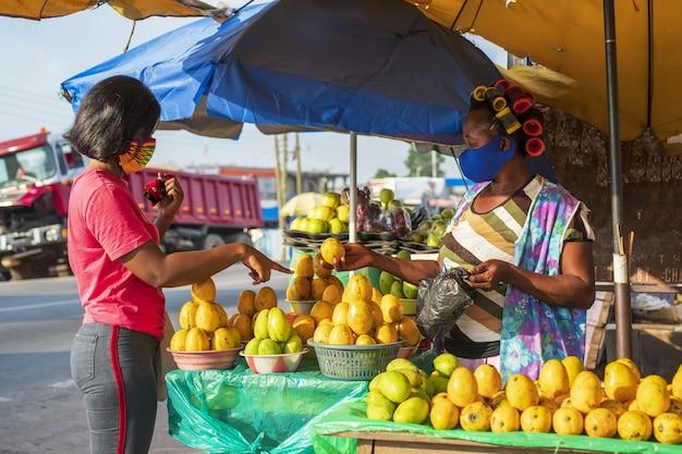 Donna afroamericana con una maschera protettiva per il viso che fa shopping in un mercato della frutta
