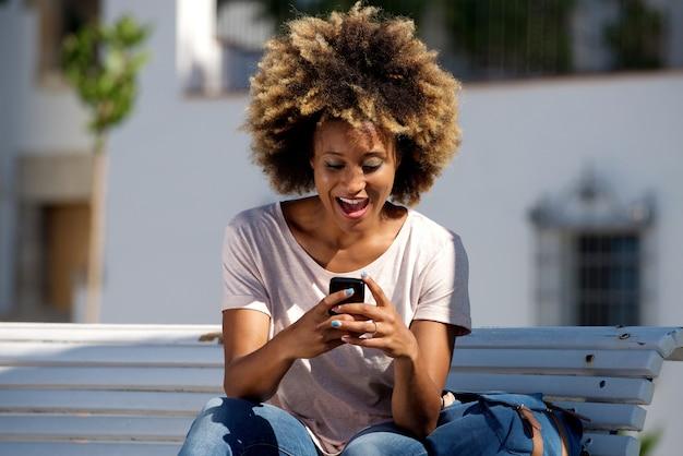 아프리카 계 미국인 여성 앉아 야외에서 스마트 폰 문자 메시지를 읽고