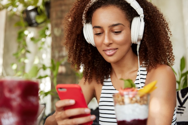 アフリカ系アメリカ人の女子学生は、居心地の良いカフェで無線インターネットに接続されているスマートフォンの現代のヘッドフォンでオーディオのレッスンを聞いて、外国語の知識を向上させます。テクノロジーと若者