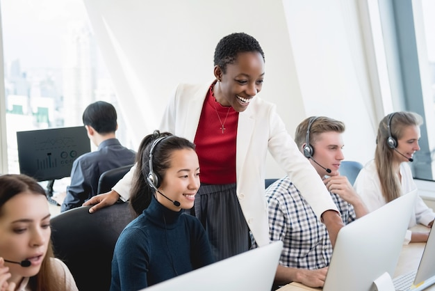 African american female supervisor training work to multiethnic team in call center