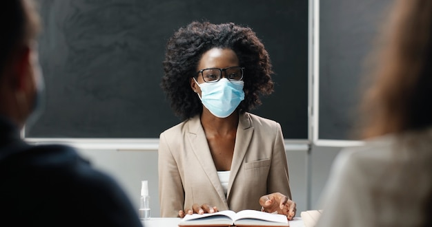 African american female teacher in glasses and medical mask sitting at table in school at class, reading textbook and teaching. literature lesson. woman educator asking questions of students or pupils