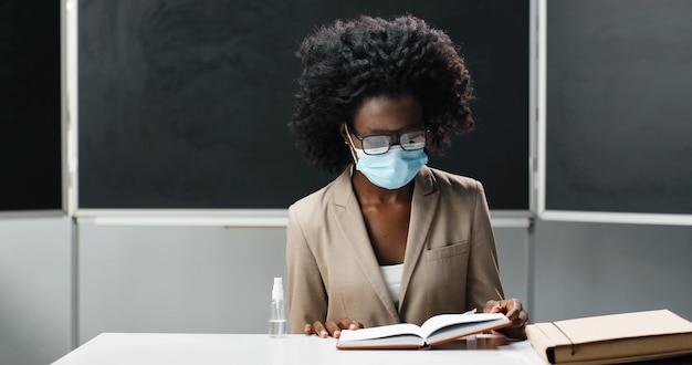 Афро-американская учительница в очках и медицинской маске сидит за столом в школе в классе, читает учебник и преподает. урок литературы. педагог женщина задает вопросы студентов или учеников