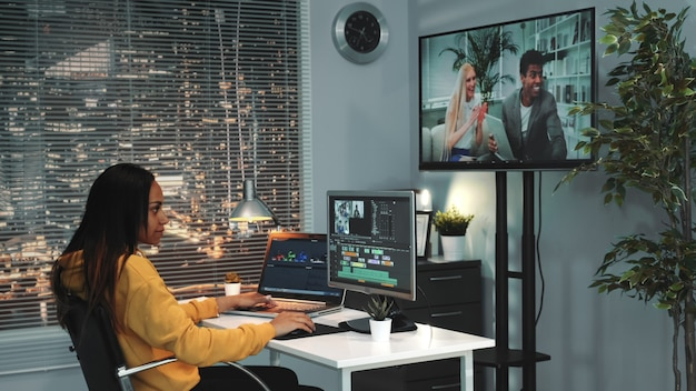 アフリカ系アメリカ人の女性のビデオエディターはコンピューターで動作し、異なるフレームからビデオをマウントします