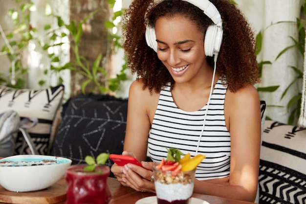 African american female with bushy hairstyle, listens online radio broadcast in headphones, connected to wireless internet in cafe, eats delicious dessert. people, technology, leisure concept