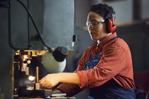 공장에서 기계를 사용 하여 아프리카 계 미국인 여성 노동자