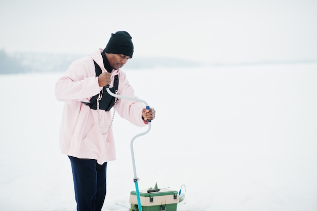 African american fisherman making hole in frozen ice by drill. winter fishing.