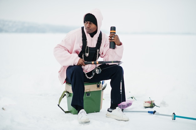 African american fisherman with fishing rod and thermos. winter fishing.