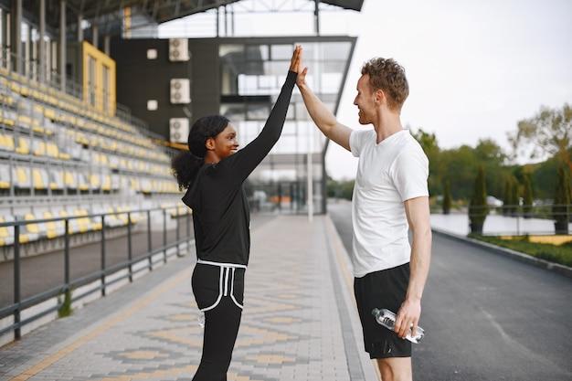 アフリカ系アメリカ人のフィットネスモデルと白人男性が屋外でトレーニング中にハイタッチをする