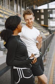 アフリカ系アメリカ人のフィットネスモデルと屋外でトレーニングしながら話している白人男性