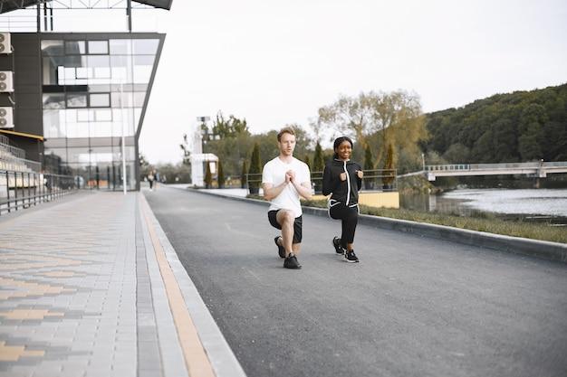 アフリカ系アメリカ人のフィットネスモデルと白人男性の屋外トレーニング