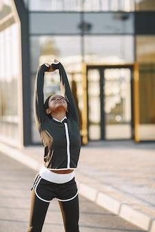 Афро-американская фитнес-модель растягивается на открытом воздухе