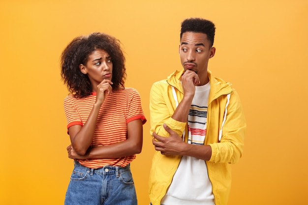 Афро-американские друзья смотрят друг на друга с любопытным выражением лица
