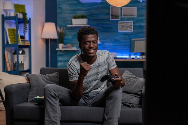 아프리카계 미국인 게이머 승자가 온라인 비디오 게임을 하고 우주 사수를 이깁니다.