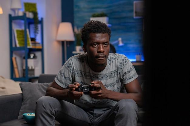온라인 비디오 게임을 하는 게임 컨트롤러를 들고 있는 아프리카계 미국인 게이머 청년