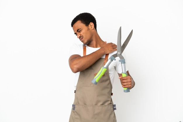 African american gardener man holding pruning shears over isolated white background suffering from pain in shoulder for having made an effort