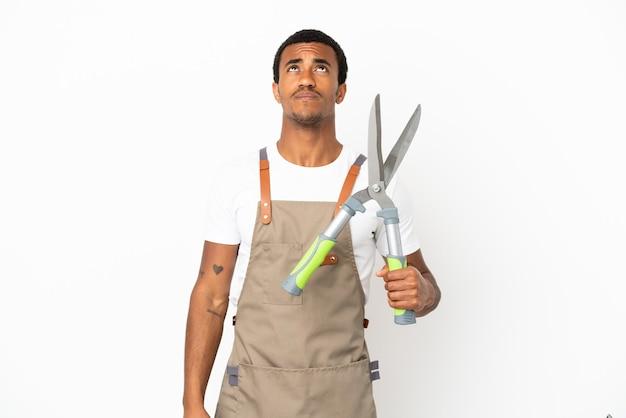 孤立した白い背景の上に剪定ばさみを保持し、見上げるアフリカ系アメリカ人の庭師の男