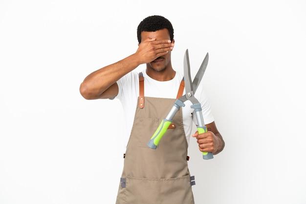 Афро-американский садовник мужчина держит секатор на изолированном белом фоне, закрывая глаза руками. не хочу что-то видеть