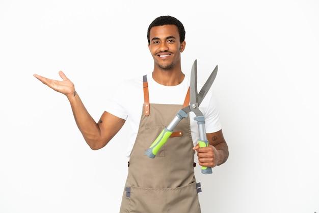 Афро-американский садовник, держащий секатор на изолированном белом фоне, протягивает руки в сторону, приглашая приехать