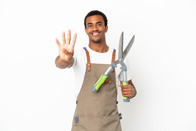 Афро-американский садовник, держащий секатор на изолированном белом фоне, счастлив и считает четыре пальцами
