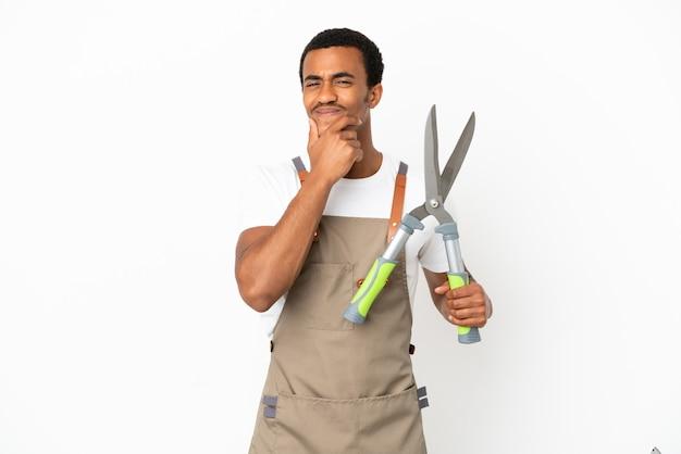 Афро-американский садовник, держащий секатор на изолированном белом фоне, счастлив и улыбается