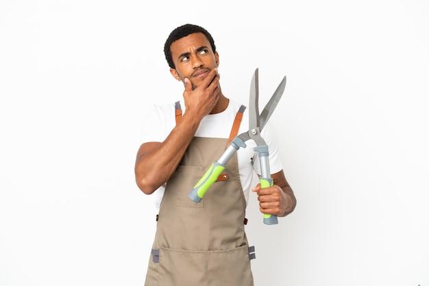 笑顔で見上げる孤立した白い背景の上に剪定ばさみを保持しているアフリカ系アメリカ人の庭師の男