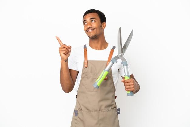 Афро-американский садовник, держащий секатор на изолированном белом фоне, указывая на отличную идею
