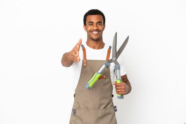 Афро-американский садовник, держащий секатор на изолированном белом фоне, пожимая руку для заключения хорошей сделки
