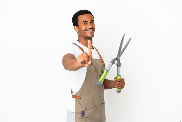 Афро-американский садовник, держащий секатор на изолированном белом фоне, показывает и поднимает палец