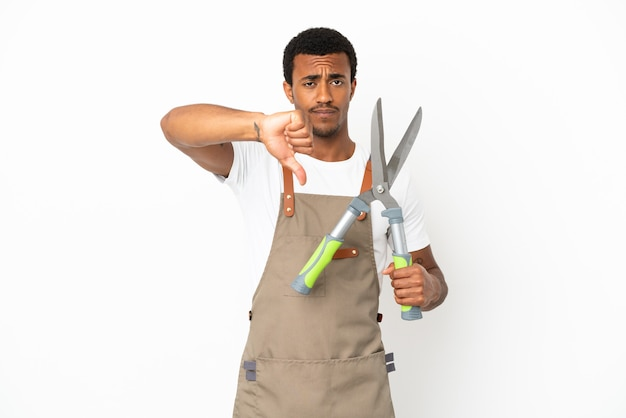 고립 된 흰색 배경 위에 가지 치기 가위를 들고 부정적인 표정으로 엄지 손가락을 보여주는 아프리카 계 미국인 정원사 남자