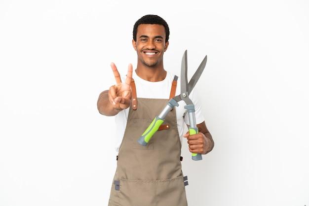 Афро-американский садовник, держащий секатор на изолированном белом фоне, улыбается и показывает знак победы