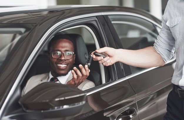 An african american gets keys from a car at a car dealership.