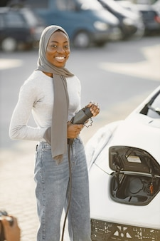 African american girl charging electro car at the electric gas station