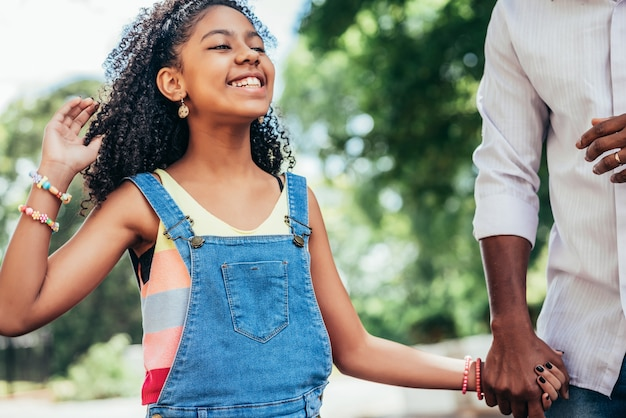 African american girl enjoying a day outdoors with her father while they hold hands and walk down the street.