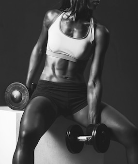 African american girl fitness trainer with dumbbells doing exercises