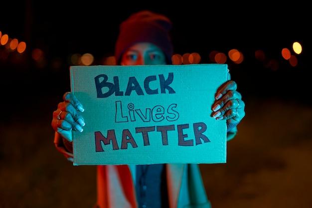 「ブラック・ライヴズ・マター」と書かれたバナーを持ったアフリカ系アメリカ人の女の子。警察の残虐行為、人種差別、および警察官による致命的な武力行使に対するデモ。