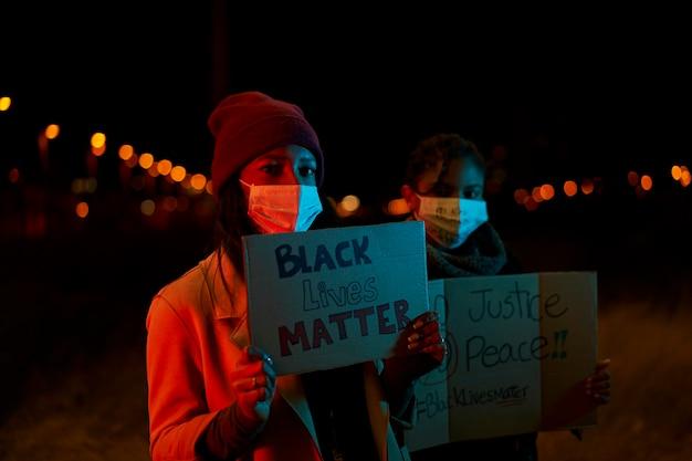 Афро-американская девушка держит знамя, стоя в толпе протестующих.