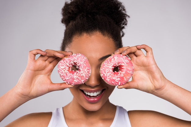 African american girl holding donut isolated.