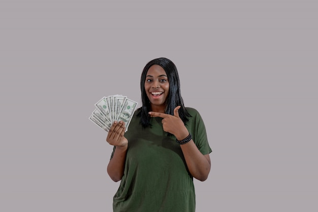 African american girl pointing hand at dollar money banknotes and smiling