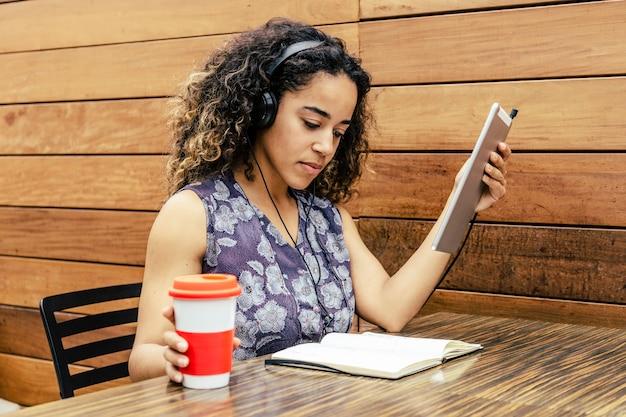 一杯のコーヒーで試験を準備し、タブレットで音楽を聴くアフリカ系アメリカ人の女の子