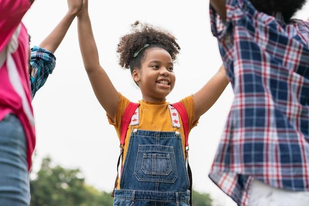 아프리카 계 미국인 여자는 공원에서 그녀의 친구와 함께 손을 제기