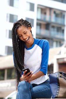 휴대 전화 야외에서 문자 메시지를 읽고 아프리카 계 미국인 여자