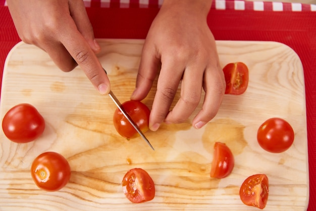 African american girl slices tomatoes on kitchen board.
