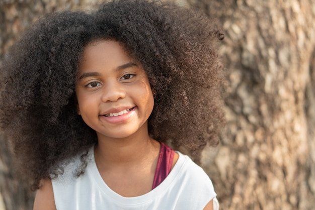 African american girl smiling and looking at camera in the park