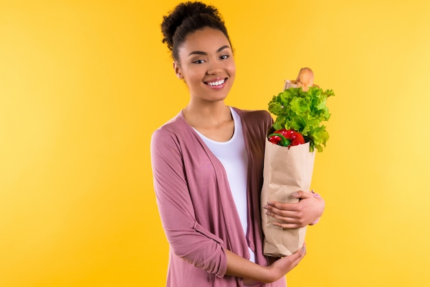 African american girl in sweater with groceries isolated.