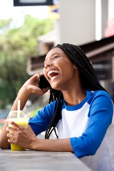 African american girl talking on mobile phone and laughing at cafe