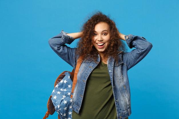 Афро-американская девушка-подросток-студент в джинсовой одежде, рюкзак положил руку за голову, изолированную на синей стене