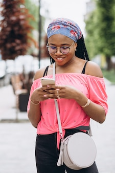 African american girl using her mobile phone on the street