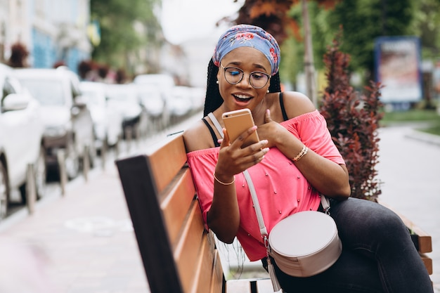 African american girl using her mobile phone while sitting on wooden bench